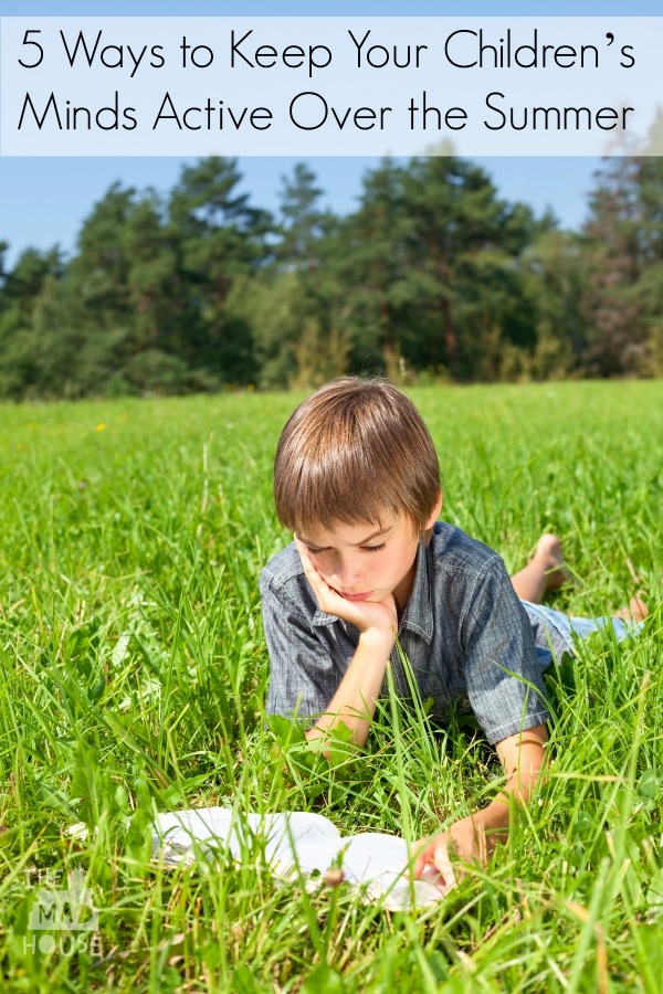 Boy lying in grass reading a book in a summer field