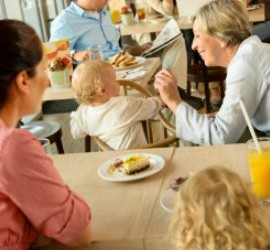 Mother and grandmother with children at cafe eating cake women
