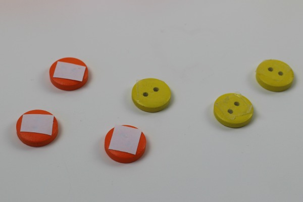 6 Orange and yellow buttons , the orange ones with double sided tape on the back