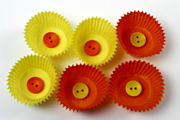 3 Orange cake cases with buttons in the center and 3 yellow ones with buttons in the center to make daffodil flower petal