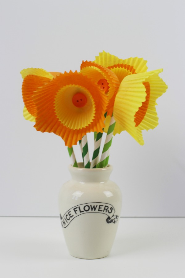 A  number of yellow and orange cake cases layered to look like daffodil flowers with buttons in the center  and paper straws as stems
