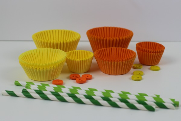 A selection of yellow and orange cake and bun cases, yellow and orange buttons and green striped paper straws to make cake case daffodils