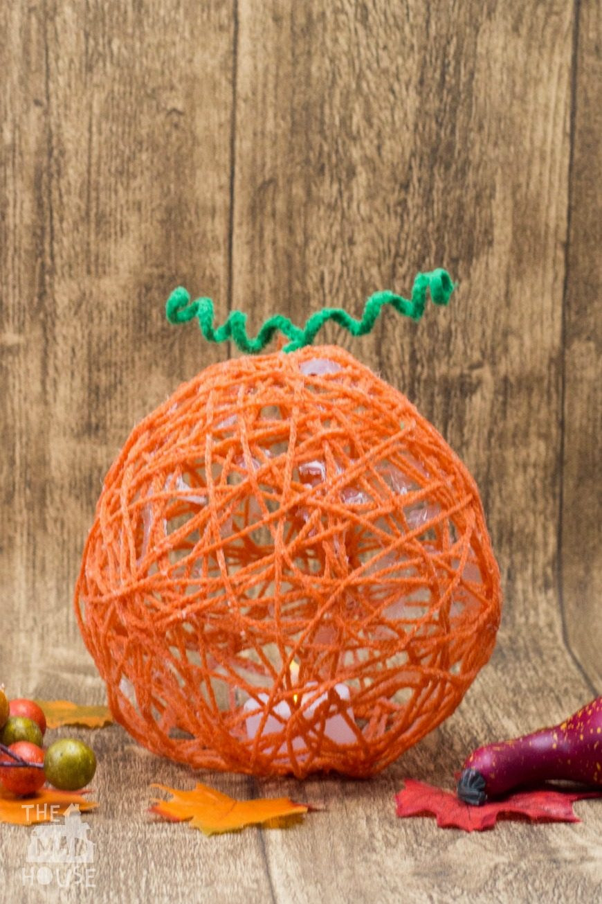 These yarn wrapped pumpkin lanterns are a fantastic fun hands-on art activity for kids. Celebrate the seasons with this autumnal craft. This is such a fun Fall themed process art activity for children.