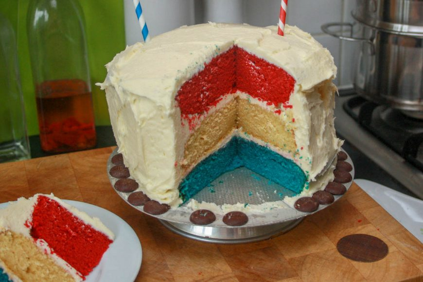 Red, white and blue layer cake with a white exterior and tiny union jack bunting hung on straws to celebrate the queens Jubilee