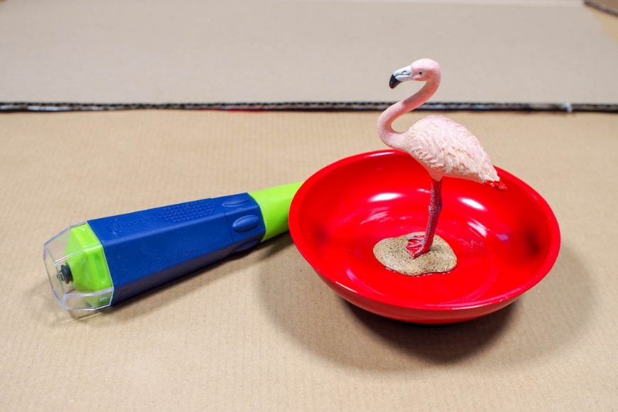 A red bowl with a pink plastic flamingo glued in the center