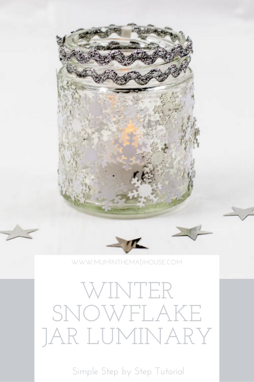 Glass jar with snowflake sequins on and two rows of silver rick rack on the top