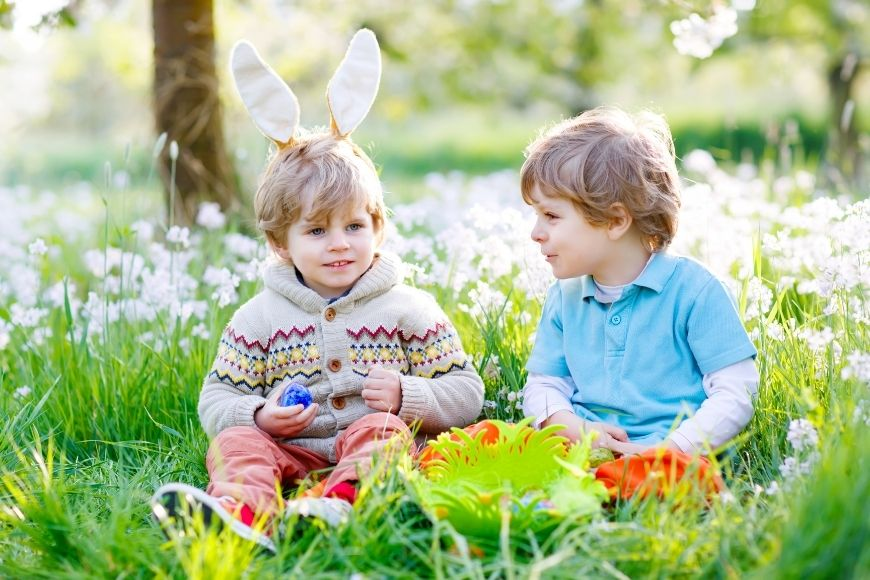 Two small boys, one with bunny ears sat in the grass with their easter eggs