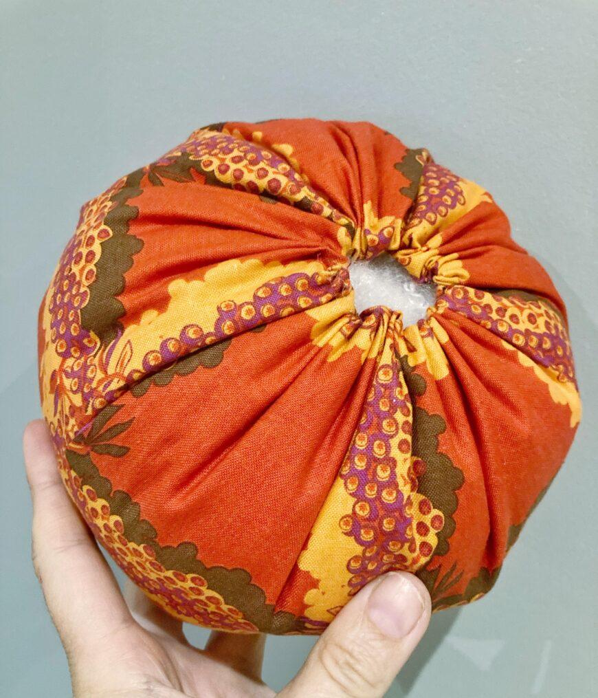An orange fabric pumpin being stuffed
