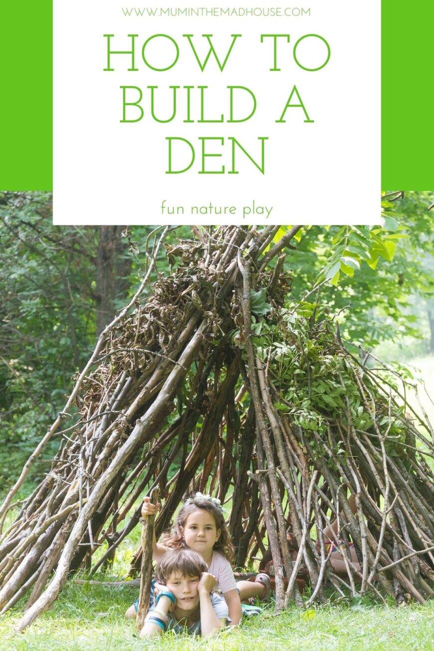 Two children laid on the ground , one with a stick under a tent made of sticks like a den