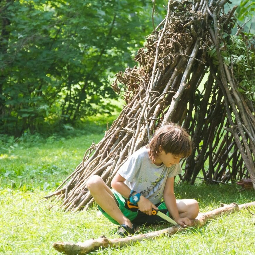 Young boy cutting branches with a hand saw in front of a tent structure made from twigs, branches and leaves